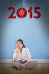 Composite image of businesswoman sitting cross legged thinking