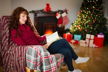 Smiling redhead reading on the armchair at christmas