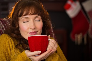 Beautiful redhead enjoying hot drink at christmas