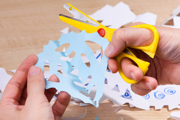 Christmas paper snowflake in women's hands.