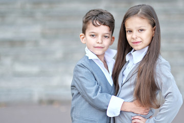 Portrait of a boy and a girl in school suit