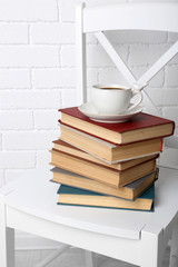 Pile of books with cup of hot drink
