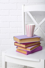 Pile of books with cup on the chair on brick wall background