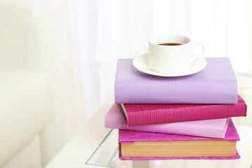 Purple books with cup near sofa