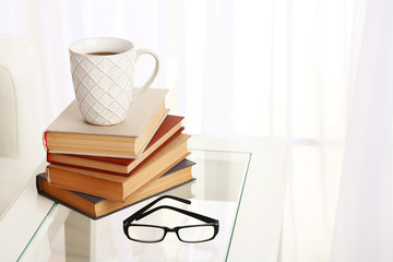 Tabletop with pile of books, cup and glasses near the sofa