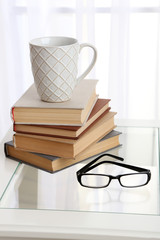 Tabletop with pile of books, cup and glasses