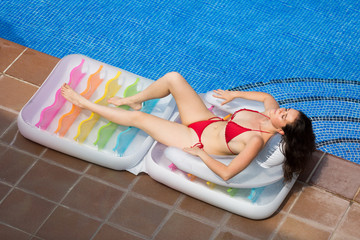 girl resting in air mattress near pool