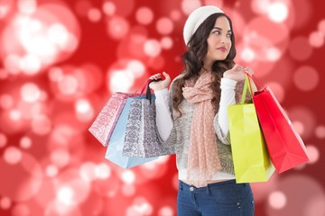 Composite image of thoughtful brunette with shopping bags