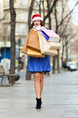 Happy woman with purchases at street