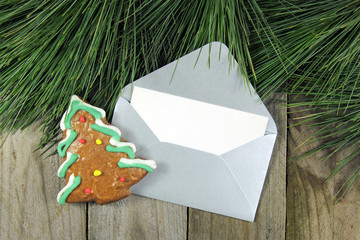 christmas fir tree, silver envelope with gingerbread on wood