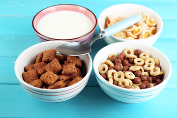 Various sweet cereals in ceramic bowls and bowl with milk