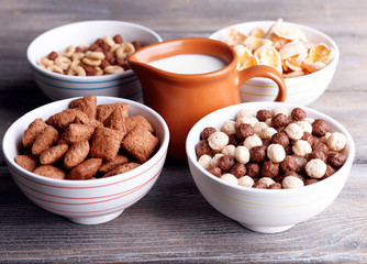 Various sweet cereals in ceramic bowls and jug with milk