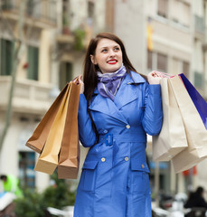 happy woman in blue with shopping bags