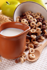 Various sweet cereals in ceramic bowl, fruits and jug with milk