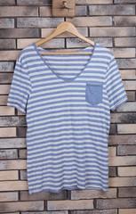 Male t-shirt on hanger on bricks wall background