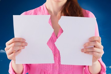 Composite image of woman holding torn sheet of paper