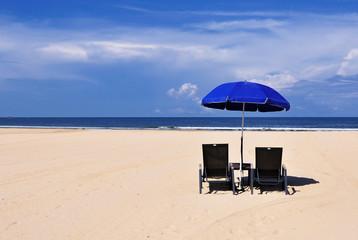 Beach chairs and blue umbrella on a sand beach