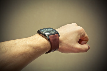 Brutal man's hand with a wristwatch. Photo toned yellow