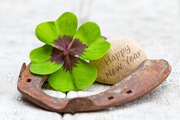Glücksbringer und Stein auf Holz, Happy New Year