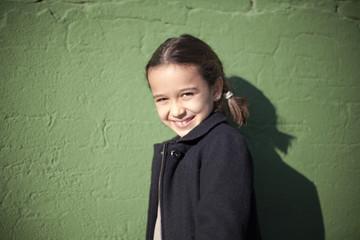 Niña con trenzas apoyada en pared verde