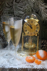 New Year's still-life with hours and champagne and tangerines
