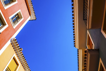 Spanish buildings in blue skies - with design / text space.