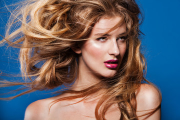 Photo of beautiful woman with magnificent hair  on blue