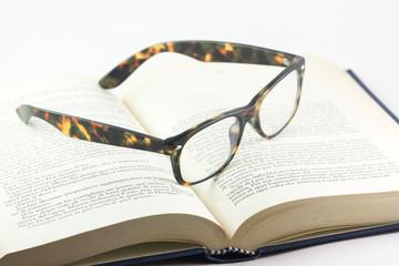Libro e un paio di occhiali aperti