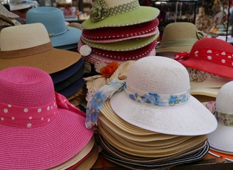 Colorful straw hats with ribbons on a market