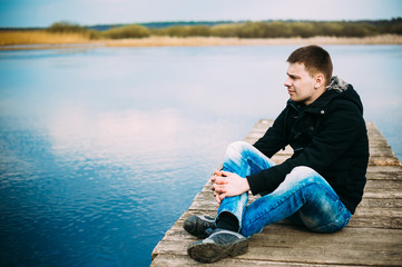 Young handsome man sitting on wooden pier, relaxing,  thinking,