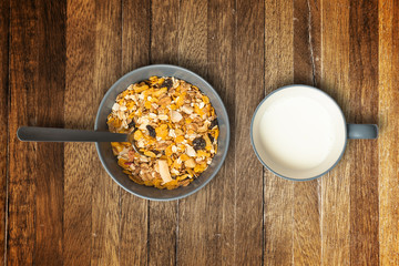 Bowl of muesli and cup of milk. Wood background.