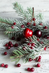 Cranberries, cherries and Christmas tree branches on a wooden ta