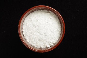 A bowl of common salt isolated on the dark background