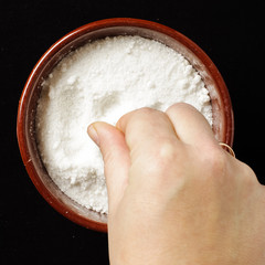 Food preparation concept female hand holding pinch of salt