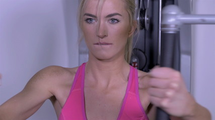 Portrait of beautiful blonde girl working out on multi gym.