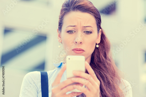 Upset woman holding cellphone disgusted with message received - 74801014