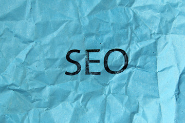 concept of SEO word on blue crumpled paper