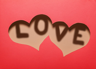 "Two hearts cutout in red paper with word ""LOVE"" inside."