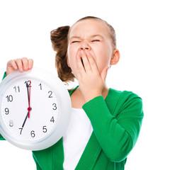 Cute girl is holding big clock