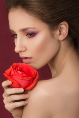 Close-up portrait of young beautiful woman holding red rose