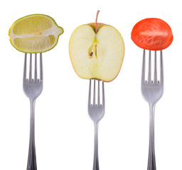 lime, apple and tomato on a fork