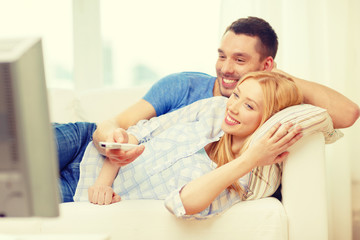 smiling couple watching movie at home