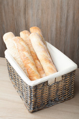 Loafs of traditional French bread baguette stocked in woven bask