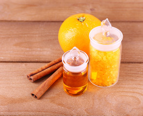 Bottles of essential oil and bath salt with orange and cinnamon