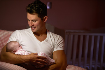 Father At Home Cuddling Newborn Baby In Nursery