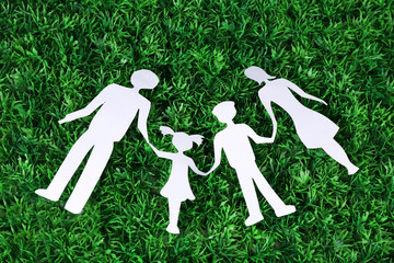 Paper family lying on green grass background