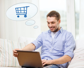 smiling man with laptop shopping online at home