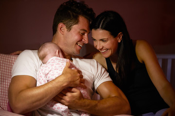Parents At Home Cuddling Baby Daughter In Nursery