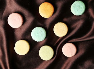 Gentle colorful macaroons on color fabric background
