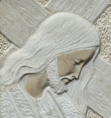 closeup of Jesus holding a cross- detail of relief in stone